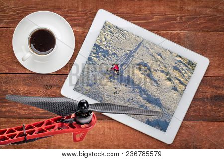 Riding a fat bike on a desert trail, reviewing an aerial image on a digital tablet with a cup of coffee
