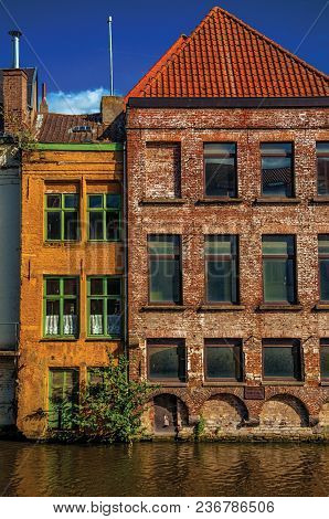 Old Buildings In Front Of The Canal With Blue Sky In Ghent. In Addition To Intense Cultural Life, Th