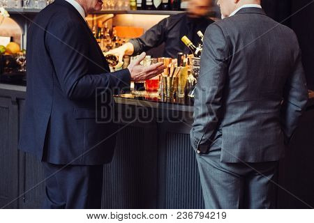 Two Adult Successful Businessmen Discuss And Talk About Business Deal In The Bar While They Drinking