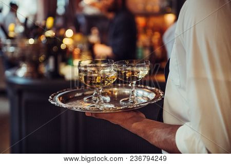Waiter From Catering Service Carrying Champagne Wine Drinks On The Tray At Event