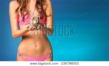 Girl in a pink bathing suit on a blue background