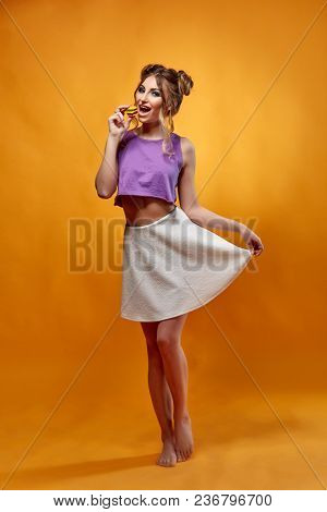 Cheerful young woman stands with fruit jelly candies on a pink background. Pin up style.