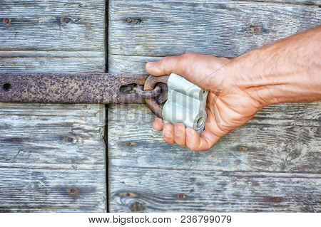 Mans Hand Holding An Old Lock On A Wooden Door. Close View