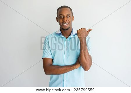Cheerful Successful African Man Pointing Aside And Looking At Camera. Optimistic Confident Handsome