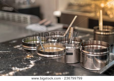 Food Ingredients On Stainless Containers Near Hot Flat Pan In Restaurant