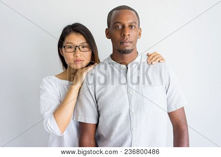 Calm Beautiful Young Interracial Couple Looking At Camera. Serious Asian Girl Supporting Boyfriend A