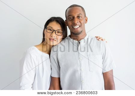 Cheerful Jolly Young Interracial Couple Looking At Camera. Smiling Calm Asian Girl Leaning Head On B
