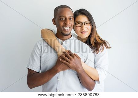 Happy Interracial Couple Embracing And Looking At Camera. Cheerful Attractive Asian Girl In Eyeglass