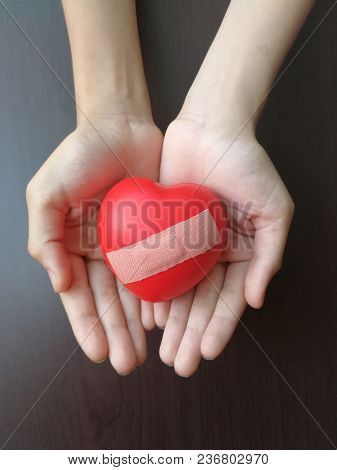 Wounded red heart in hand