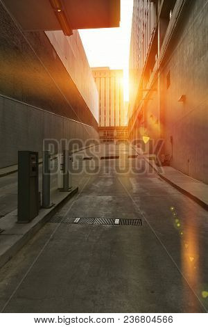 A dark narrow concrete alley with security gate and dramatic golden sunglare.