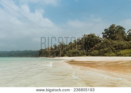 Idyllic Tropical Beach With Clean White Sand And Green Island On Front. On A Hot Tropical Summer Day