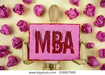 Handwriting text Mba. Concept meaning Master of Business Administration Advance Degree After College Studies written Sticky Note paper holding by Wooden Robot Toy plain background Paper Balls. poster