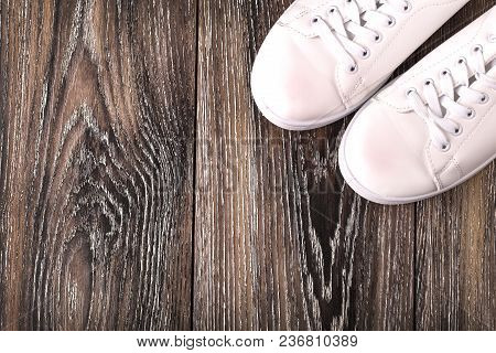 White Sneakers On Dark Wooden Surface. Shoes For Women In Sport Fashion Style.