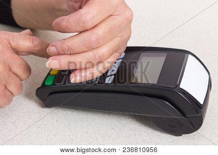 Elderly Senior Woman Covering Hands Whilst Entering Personal Identification Number On Payment Termin