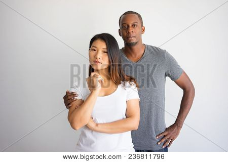Handsome African American Man Hugging Chinese Girlfriend. Portrait Of Young Mixed Raced Couple Posin