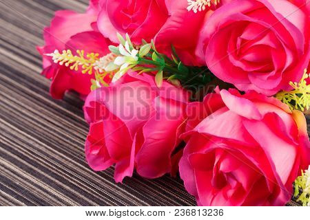 Red Fabric Roses On Striped Cloth Background, Closeup Picture.