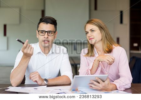 Confident Businessman Talking To Female Colleague At Briefing. Young Caucasian Manager Wearing Glass