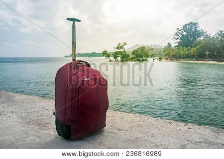 Travel Concept. Suitcases On Seascape Background. Suitcase On Wheels Stands On The Pier In The Port.