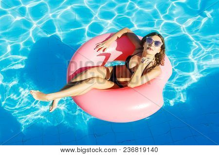 Beautiful Happy Woman With Inflatable Ring Relaxing In Blue Swimming Pool.