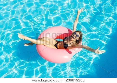 Beautiful Crazy Woman Relaxing On Inflatable Ring In Blue Swimming Pool.