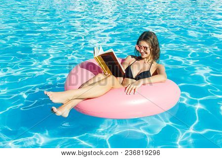 Beautiful Crazy Woman Reading A Book On Inflatable Ring In Blue Swimming Pool.
