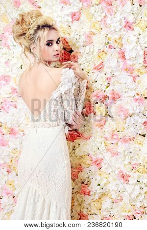 Portrait of a beautiful bride woman posing by background of roses. Wedding make-up and hairstyle. Jewellery.