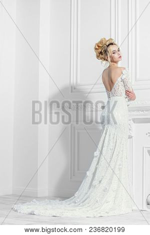 Full length portrait of a magnificent young woman in elegant long white dress. Luxurious apartments.  Wedding fashion.
