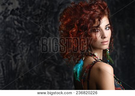 Beautiful bright woman with curly foxy hair wears a beads and earrings in boho style. Ethnic style in accessories.