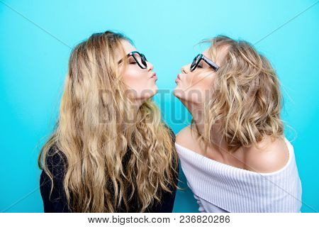 Two pretty cheerful girls in glasses are posing in studio over blue background. Beauty, fashion. Optics, eyewear.