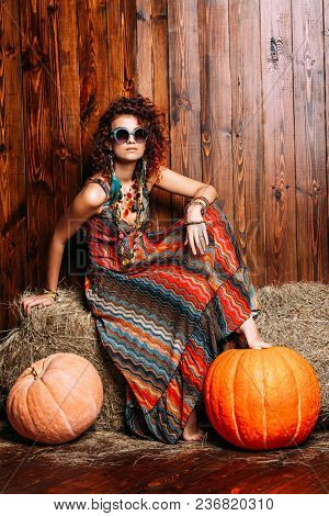 Beautiful bright woman with curly foxy hair sits on a haystack. Dress and accessories in boho style. Ethnic style in clothes.