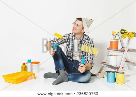 Man In Newspaper Hat Sitting On Floor With Paint Rollers, Instruments For Renovation Apartment Room