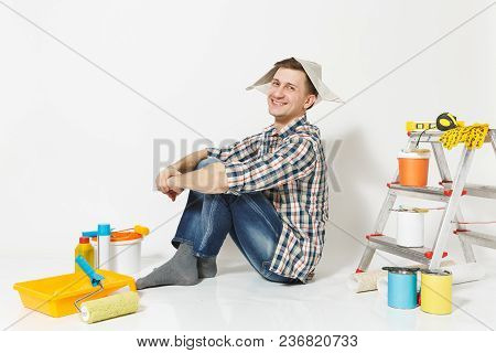 Fun Happy Smiling Man In Newspaper Hat Sitting On Floor With Instruments For Renovation Apartment Ro
