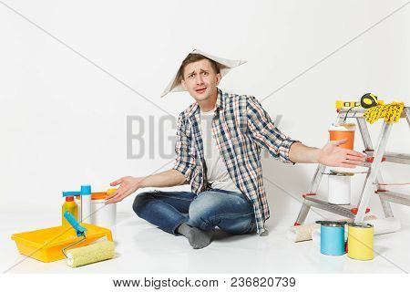 Confused Shocked Man In Newspaper Hat Spreading Hands, Sitting On Floor With Instruments For Renovat