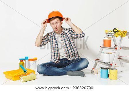 Fun Crazy Man In Orange Protective Helmet Sitting On Floor With Instruments For Renovation Apartment