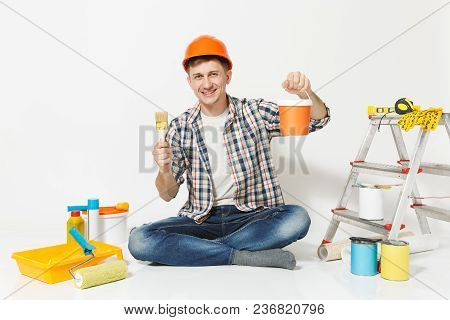 Man In Orange Protective Helmet Sitting With Paint Brush, Can, Instruments For Renovation Apartment