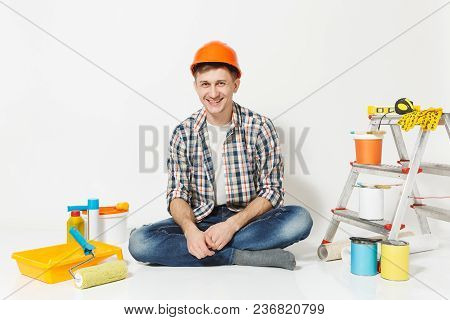 Smiling Male In Orange Protective Helmet Sitting On Floor With Instruments For Renovation Apartment