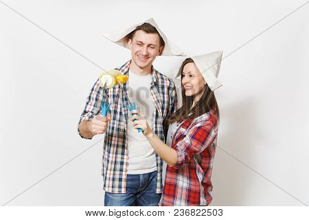 Young Happy Woman, Man In Casual Clothes Holding Paint Rollers For Wall Painting. Couple Isolated On
