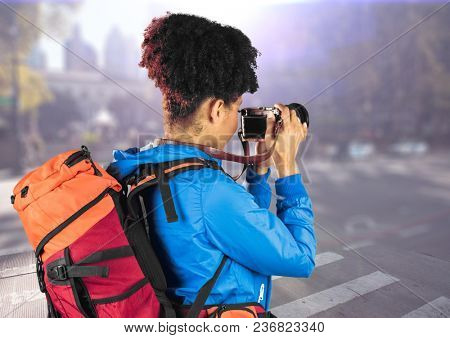 Millennial backpacker with camera against blurry street with flare