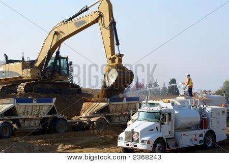 Power shovel loads trucks on site of new highway construction poster