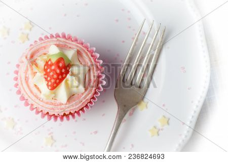 Pink Strawberry Cupcake On White Plate With Star Sprinkles , Overhead