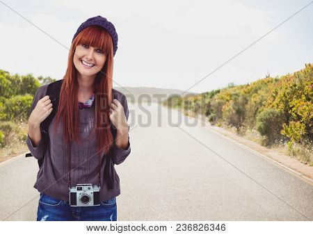Millennial backpacker smiling against road on sunny day