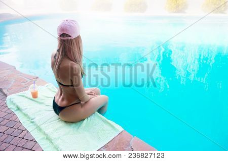 Young Wet Girl With Perfect Female Body In Black Bikini Sits With Arms Behind Her Back, At The Edge