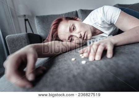 Serious Illness. Mournful Stressful Painful Woman Lying On Couch While Consuming Antidepressant And