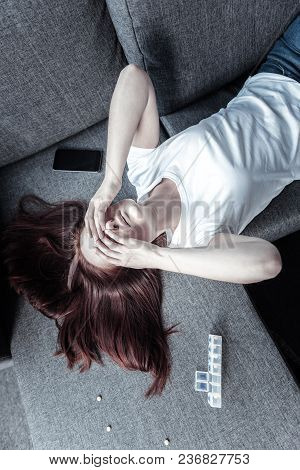 More Than Grieving. Top View Of Stressful Dreary Young Woman Covering Eyes With Hands While Resting