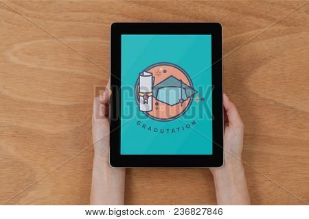 Person holding a tablet with education icon on the screen
