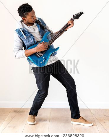 African descent man playing electric guitar