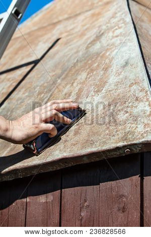 Man Grinding The Roof Of A Garden Shed With A Sanding Block, Rusty And Weathered Plate