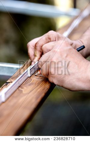 Close-up Of Hands, Wooden Plank Is Measured With The Help Of A Yardstick And Made A Mark With A Penc
