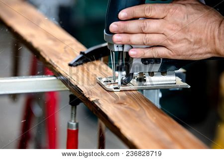 Close-up Of A Hand With Jigsaw, A Wooden Board Is Sawed Through With An Electric Hand Saw