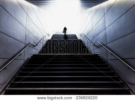 Silhouette Of Senior Man With A Walking Stick Carrying Shopping Bags Up A Long Flight Of Stairs